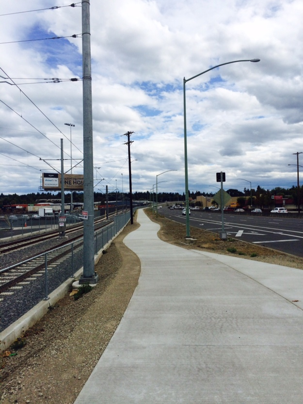 This new path separates the new rail lines from Mcloughlin Blvd. between SE 17th and Harold St. Here the concrete walk sits above the previous grade. The left edge show how high and is accomplished by 'layering' gravel base material in 'lifts' each of which are compacted for stability.