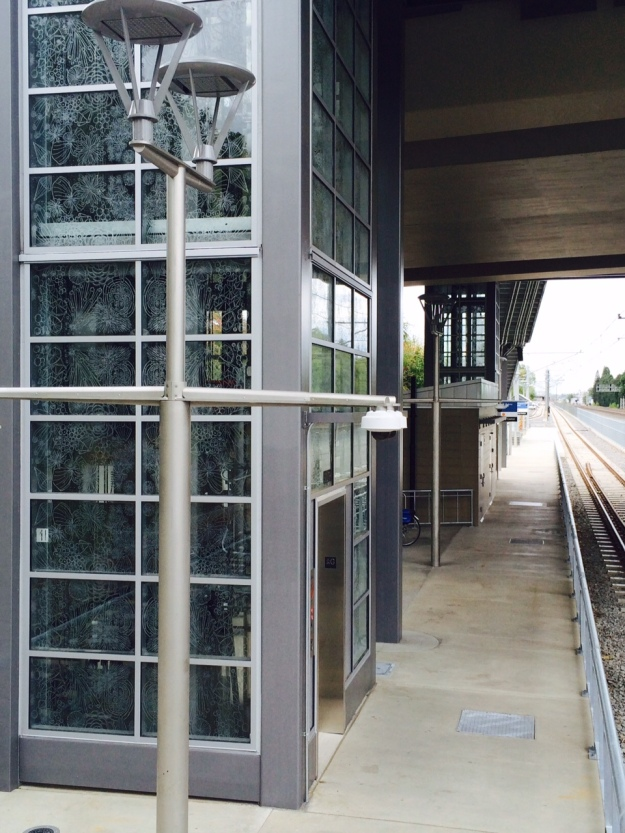 The south elevator moving passengers between the platform and the above roadway.