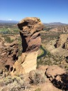 This rock column at Smith Rock is known as Monkey Face and is very well known by expert climbers. Here we're looking NW with Juniper Butte in the background to the right and Mt. Jefferson on the horizon to the left. On Monkey Face itself you can see a horizontal fracture line near the top where a roped in climber is standing. Many climbers cross from the 'horn' to the left on a rope to concentrate on the top portion of the climb while others climb from the base well out of our view.