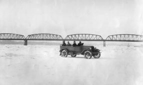 A print from the archives of The Columbian showing a car driving across the Columbia. It used to get very cold and stay that way. This combined with the absence of the dams changed flow rates and temperatures enough to allow freezing. It appears to be the railroad bridge in the background looking east with the Interstate in the distance beyond it.