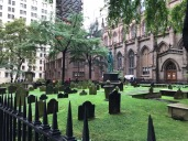 "A more idyllic New York landscape can be easily seen here, when in fact this is Trinity Church on Wall St. in the heart of NYC's financial district, a remnant of old colonial New York. It is hard to imagine when this was built, Manhattan a long low slung stretch of land wooded and still wild. Buried here are members of the Astor family; author of the ""Night Before Christmas"" Clement Clarke Moore; and author Ralph Ellison. In 1893, the Academy of Sciences erected a monument over the grave of the naturalist artist John James Audubon who had lived on an estate bordering the land the Cemetery occupies. The scale of this church and cemetary stand in contrast to the vast development that surrounds it."